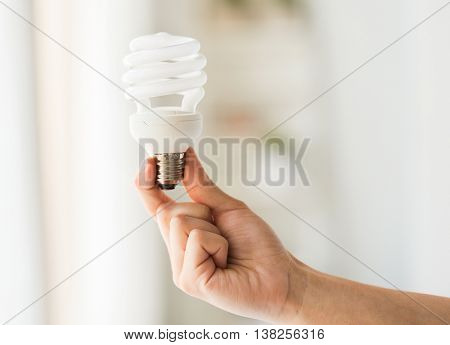 recycling, electricity, environment and ecology concept - close up of hand holding energy saving lightbulb or lamp
