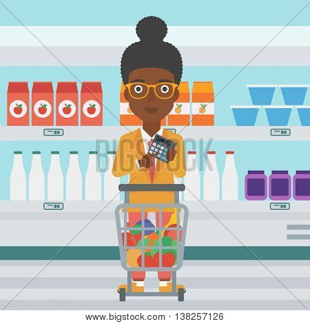 An african-american woman at the supermarket with calculator and supermarket trolley full with products. Woman checking prices with calculator. Vector flat design illustration. Square layout.
