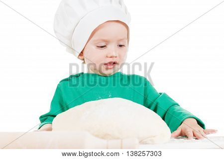 Serious little cook boy kneading the dough for the cookies isolated on white background. Half-length portrait of the table in studio
