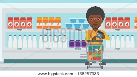 An african-american young man at the supermarket with calculator and supermarket trolley full with products. Man checking prices with calculator. Vector flat design illustration. Horizontal layout.