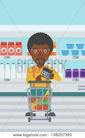 An african-american young man at the supermarket with calculator and supermarket trolley full with products. Man checking prices with calculator. Vector flat design illustration. Vertical layout.