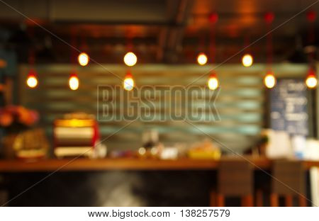 blur cafe or bar counter with hanging light lamp abstract background
