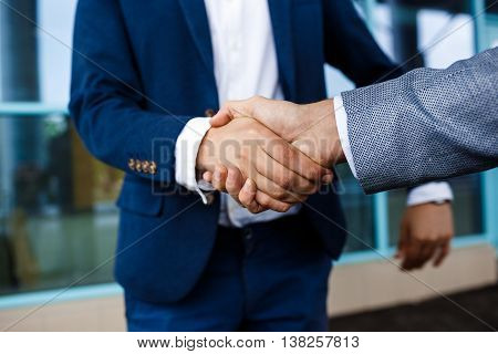 Picture of  two young businessmen on street background shake hands