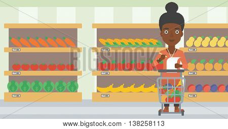 An african-american thoughtful woman standing at the supermarket with supermarket trolley full with products and holding a shopping list in hands. Vector flat design illustration. Horizontal layout.