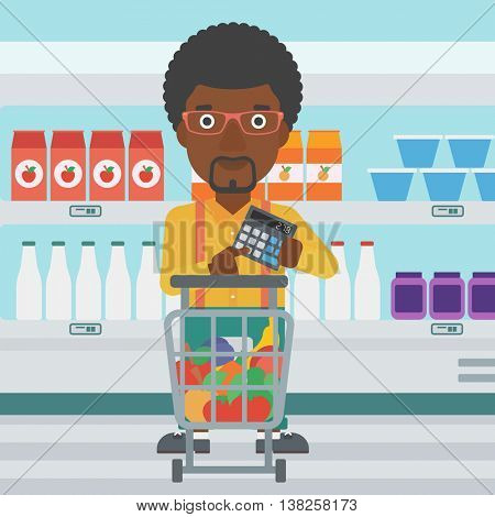 An african-american young man at the supermarket with calculator and supermarket trolley full with products. Man checking prices with calculator. Vector flat design illustration. Square layout.