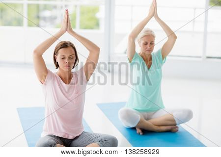 Women with hands clasped doing yoga at fitness studio