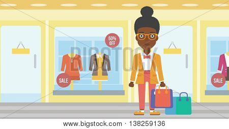 An african-american woman holding shopping bags on the background of boutique window with dressed mannequins. Happy woman carrying shopping bags. Vector flat design illustration. Horizontal layout.