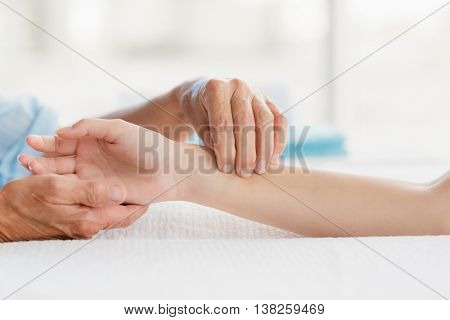 Cropped image of masseur giving hand massage to woman at spa
