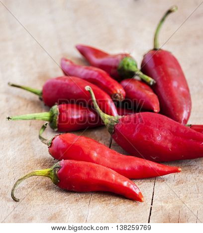 Pile of red chilli peppers on wooden background. Spicy food with copy space