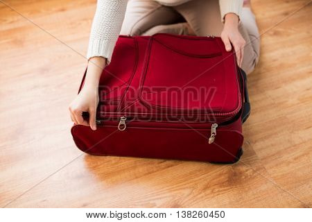 summer vacation, travel, tourism and objects concept - close up of woman packing and zipping travel bag for vacation