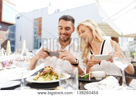 love, date, technology, people and relations concept - happy couple with smatphone taking picture of food at restaurant terrace