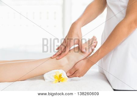 Midsection of masseur giving foot massage to woman at spa
