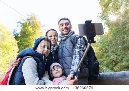 technology, travel, tourism, hike and people concept - happy family with backpacks taking picture by smartphone on selfie stick and hiking