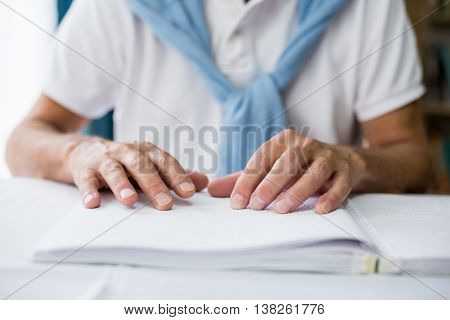 Senior man using braille to read in a retirement home
