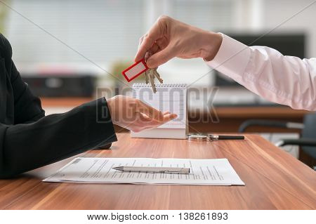 Real estate concept. Realtor is passing keys to the client sitting behind desk with contract on blurred background.