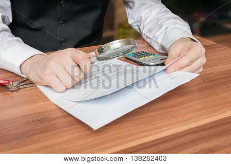 Man Holds Magnifying Glass And Is Reading Contract.