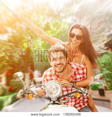 Couple in love riding a retro motorbike. Handsome guy and young sexy woman travel. Young riders enjoying themselves on trip. Adventure and vacations concept.
