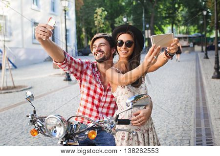couple making selfie photo on a background of the city. Fashion young woman and handsome man holding mobile phone and making self photos