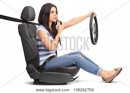 Young woman driving and putting on lipstick isolated on white background