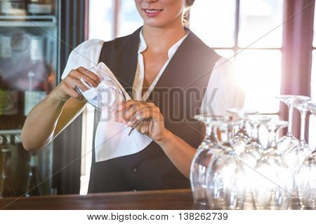 Waitress cleaning glasses in a restaurant