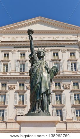 NICE FRANCE - APRIL 11 2016: Small-scale bronze replica (circa 2014) of world famous Statue of Liberty in Nice France. Commemorates 100 years since the WWI. Opera de Nice on the background