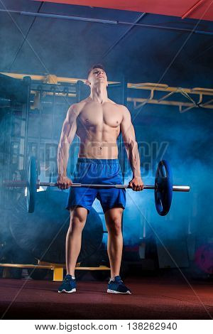 young man doing exercises with barbell in gym