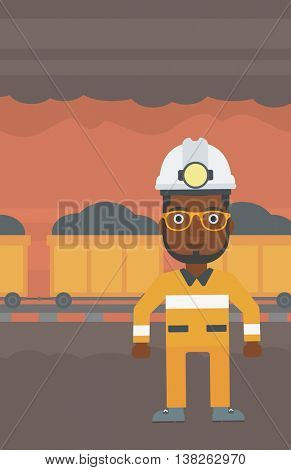 An african-american confident coal miner. Male miner in hardhat with torch. Miner standing on the background of mining tunnel with cart full of coal. Vector flat design illustration. Vertical layout.