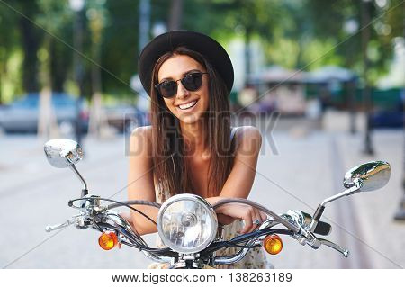 Street portrait of pretty smiling girl on motorbike. Fashion young woman wearing sunglasses and stylish hat on a retro scooter on a summer day in a cityspace.