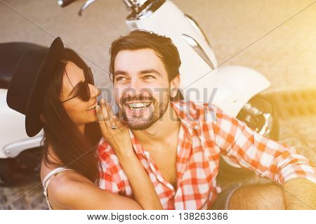 smiling young hipster couple whispering gossip while sitting near a scooter. friendship, happiness and people concept