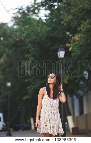 Young hipster woman in a summer dress and sunglasses looking upwards to copy space. Attractive female walking on street outdoors.