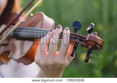 Young woman playing violin in a field at sunset