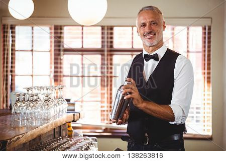 Portrait of bartender mixing a cocktail drink in cocktail shaker at bar counter