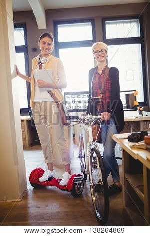 Graphic designer holding bicycle while colleague standing on hover board in office