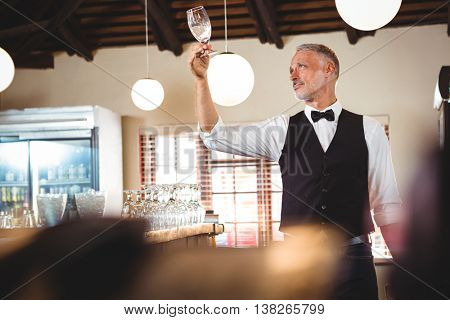 Bartender examining a clean wine glass in restaurant