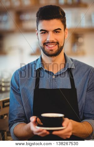 Portrait of smiling man holding cup of coffee in office cafeteria