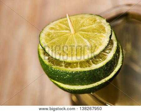 Alcohol drink. On wooden boards is glass with alcohol green transparent drink. A drink number hundred forty six of top cocktail glass decorated with slice of lime. Country life. Light background.
