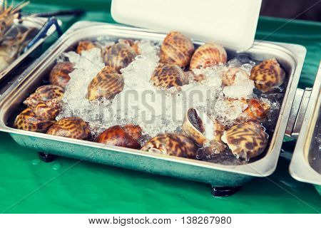 cooking, asian kitchen, sale and food concept - chilled snails or seafood on ice at street market