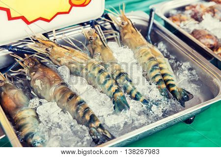 cooking, asian kitchen, sale and food concept - chilled shrimps or seafood on ice at street market