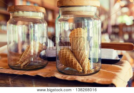 food, storage and eating concept - close up of jars with waffle cones at restaurant, bakery or grocery store