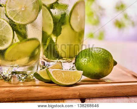 Alcohol drink. On wooden boards top of glasses with alcohol drink and ice cubes. Drink hundred forty nine cocktail mohito and quartered lime with mint leaf. Country life. Outdoor. Light background.