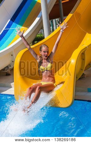 Child in yellow bikini on water slide at aquapark and hand up. There are two water slides with flowing water in aqua park. Summer holiday. Outdoor.