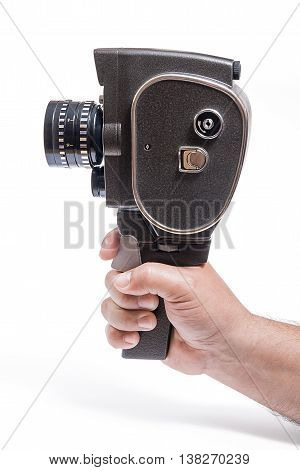Hand Holding A Vintage Movie Camera Isolated On White. With Clipping Path.