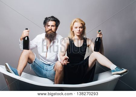 young drunk couple of blonde pretty girl and bearded man with long beard holding wine bottles sitting on bathtub on grey background