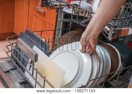 Female Hand And Dirty Plates In Dishwasher. Housework Concept.