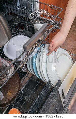 Housework Concept. Female Hand Is Putting Dirty Dish In Dishwash