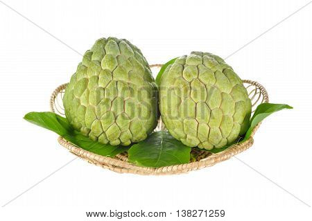 raw custard apple with leaves in rattan basket on white background
