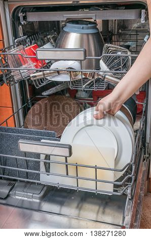 Housework Concept. Woman Is Putting Dirty Dish In Dishwasher.