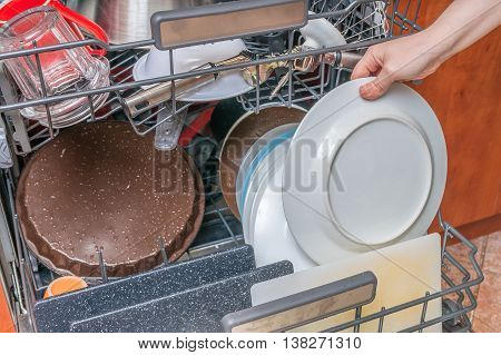 Dirty Dishes In Dishwasher And Female Hand.