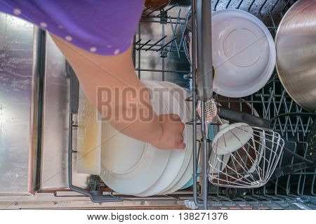 Female Hand Is Putting Dirty Dishes In Dishwasher. Top View.