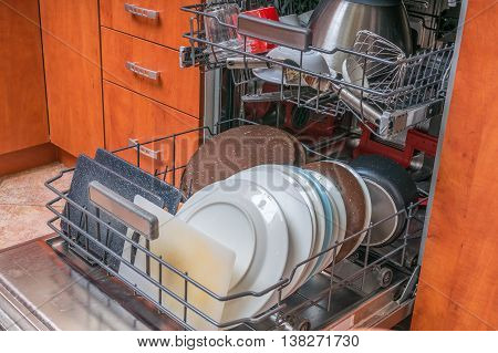 Dishwasher machine filled with dirty dishes in kitchen.
